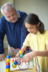Young girl using a wooden bead maze roller with adult overlooking