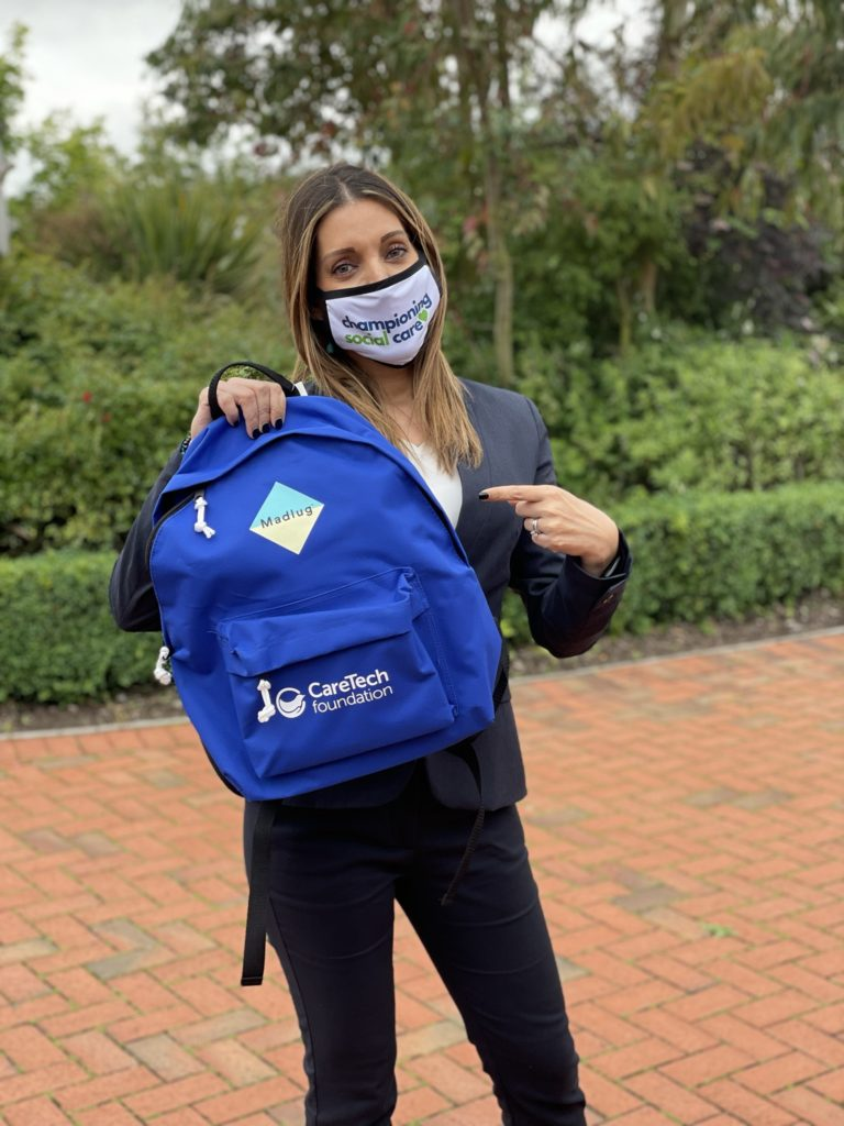 Dr Rosena Allin-Khan pictured pointing at a CareTech Foundation Madlug bag, wearing a Championing Social Care PPE mask.